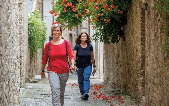 two women walking in a narrow alley