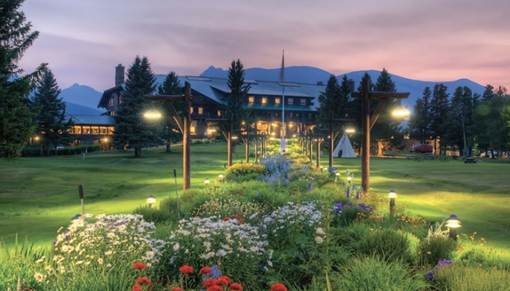 large lawn and gardens at night in front of Glacier Lodge