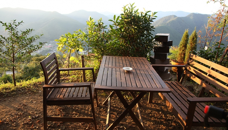 wooden table outside overlooking a forested valley