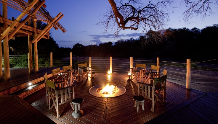 Rhino Post Safari Lodge deck with firepit at night