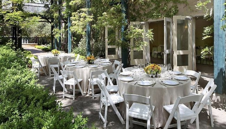 tables set at an outdoor patio with lots of plants