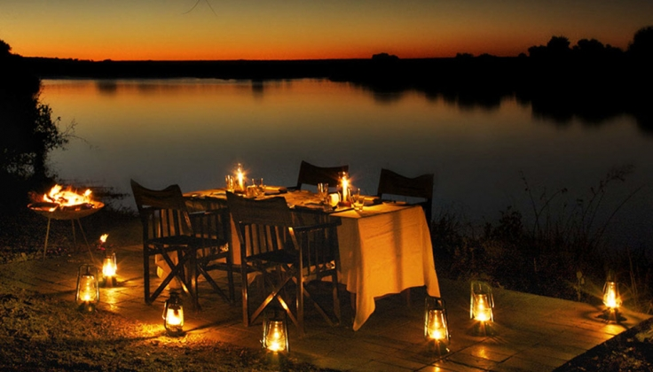candle lit table along river bank at dusk