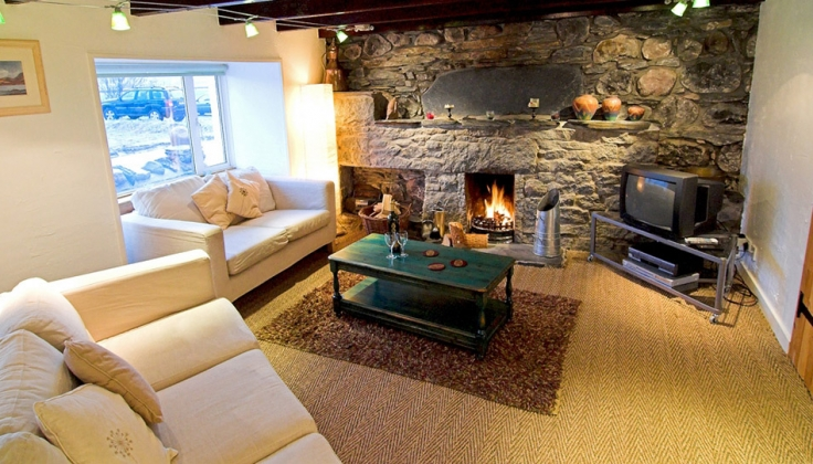 living room with stone fireplace and wooden ceiling beams