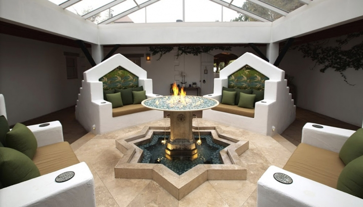 Four throne like chairs positioned around a central firepit in a room with a glass ceiling