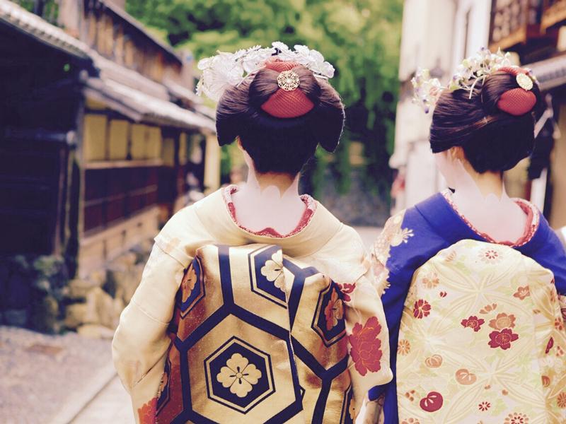 Geishas from Japan walking down a walkway