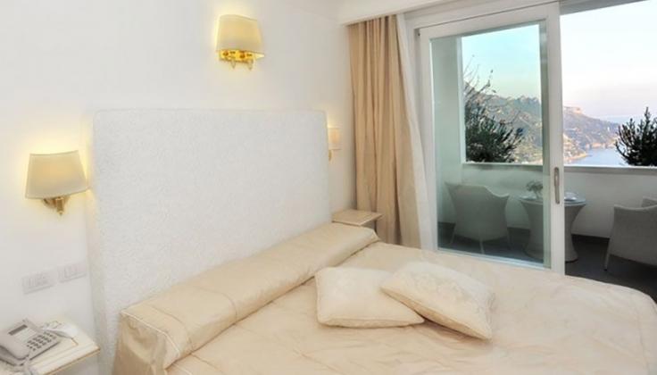 a hotel bedroom with window overlooking ocean
