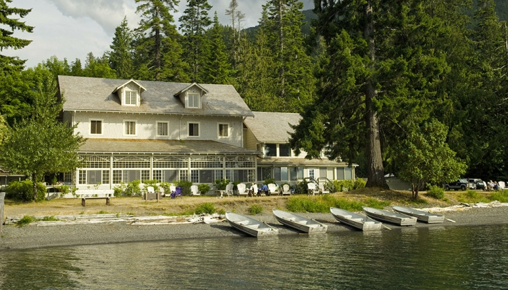 lakefront hotel lodge with trees in background and aluminum boats along the shore
