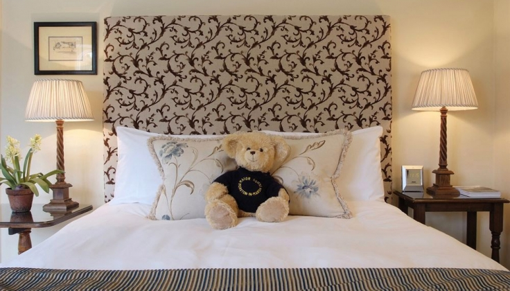 a hotel bed with teddy bear