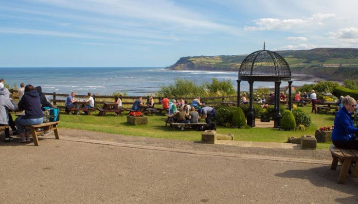 Picnic tables with people and gazebo set beside the seaside
