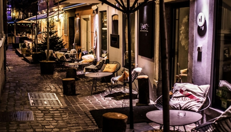 tables set out on a cobblestone alleyway at night