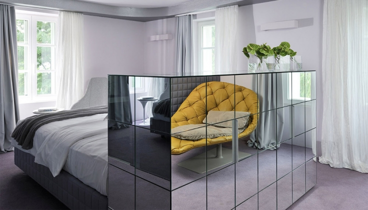 a hotel bedroom with shelving unit covered in mirrors